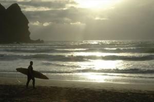 Surfař na pláži Piha Beach