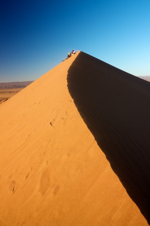 People sitting on top of dune watching sunset in Erg Chigaga desert