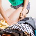 Žena klečící na svém plném batohu při jeho balení.