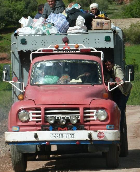 Berberští muži na korbě nákladního automobilu.