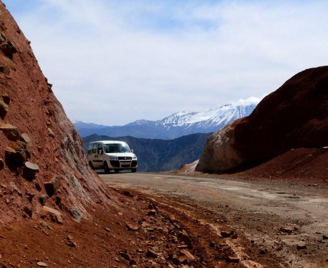 Bílý FIAT jedoucí po cestě do kopce.