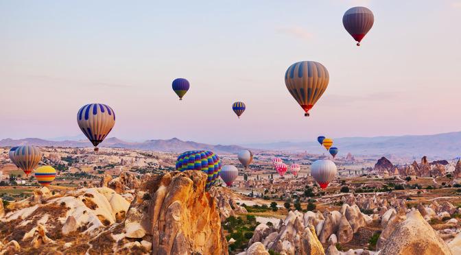 Turecko - horkovzdušné balony vznášející se nad obzorem Kappadokie