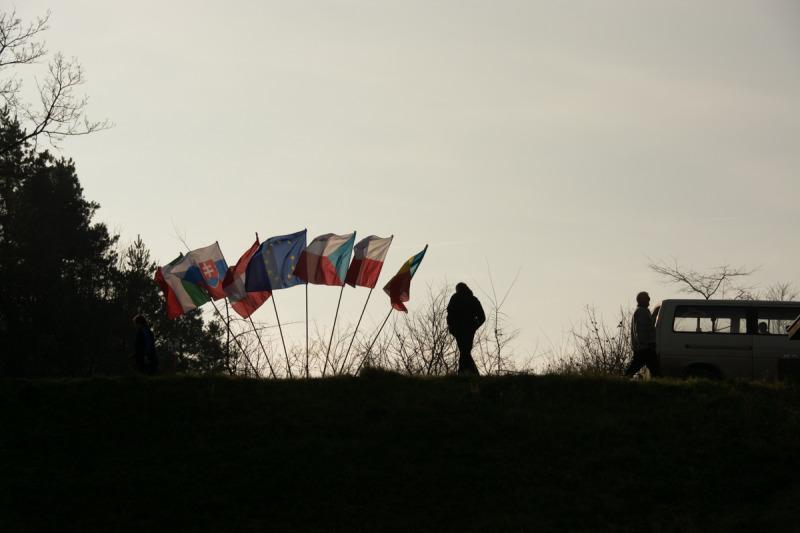 Vlajky a silutey lidí vyčkávajících startu zimního plavání.