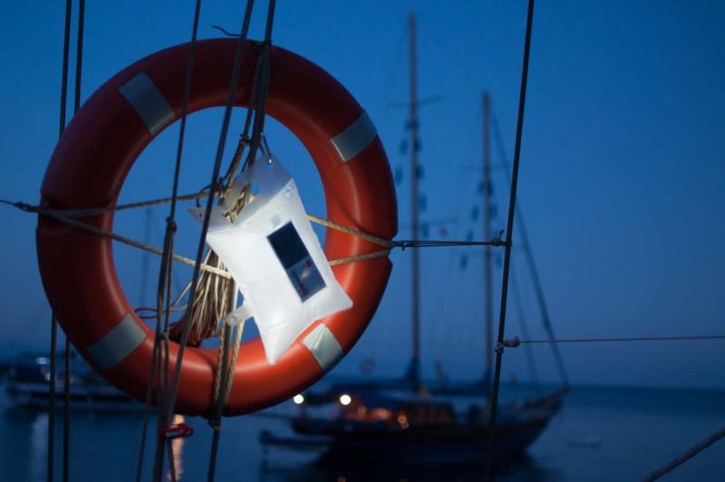 LuminAID - solární vodotěsná LED baterka v sáčku ve sbaleném stavu, zavešená na lodi.