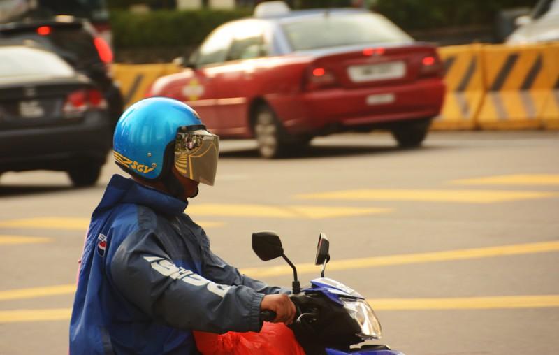 Kuala Lumpur - řidič skútru v dopravě.