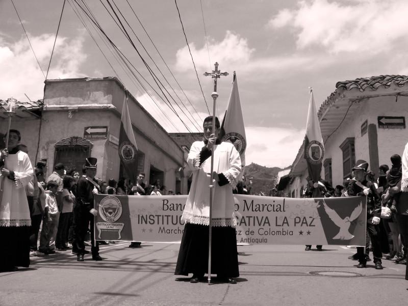 Procesí vždy začíná trojicí ministrantů nesoucích krucifix zahalený na znamení smutku. Zde se jedná o Palmovou neděli. Je tropické horko o dvaatřiceti stupních Celsia. La Ceja, Kolumbie.