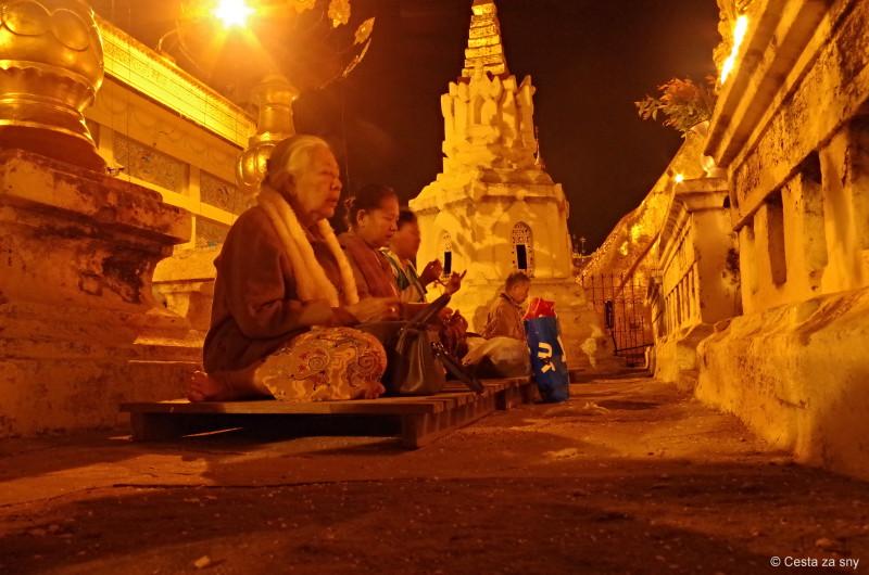 Buddhistická slavnost a místní meditující lidé.