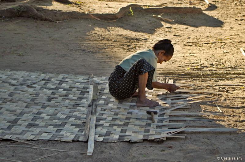 Žena vyrábí střechu z bambusu.