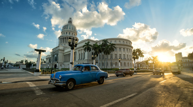 HAVANA, CUBA - NOVEMBER 05, 2016: Blue retro car and local autos are riding near the ancient colonial Capitol building in a central empty crossroad of Havana city at evening sunset time