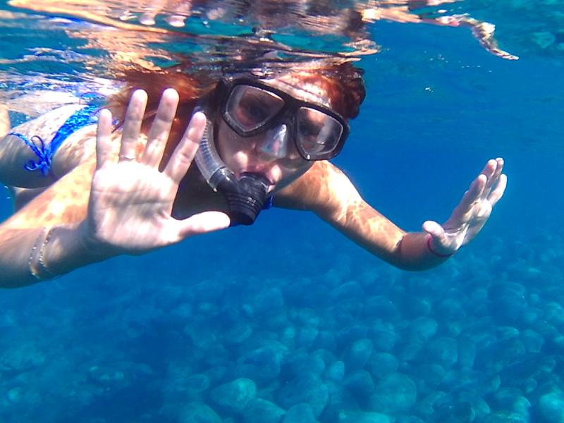 Pod vodou na ostrově La Palma. Mladá dívka v plavkách v potápečských brýlých a se šnorchlem.