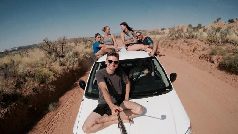 Work and travel – Jak si správně vybrat agenturu a jaký je rozdíl mezi zprostředkovateli. Parta mladých lidí na autě s akční kamerou na selfie tyči uprostřed pouště v USA.