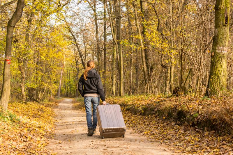 Vzít si na cesty kufr na kolečkách – šílenost nebo reálná věc? Mladá holka s kufrem na kolečkách kráčející podzimně zabarveným lesem .