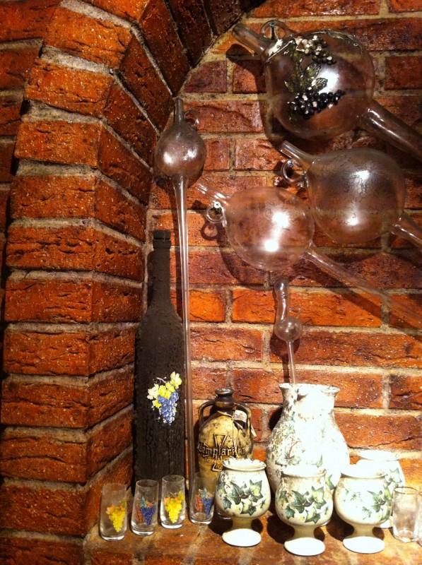 Několik koštýřů a pohárků na víno zdobí kvelbený výklenek ve zdi