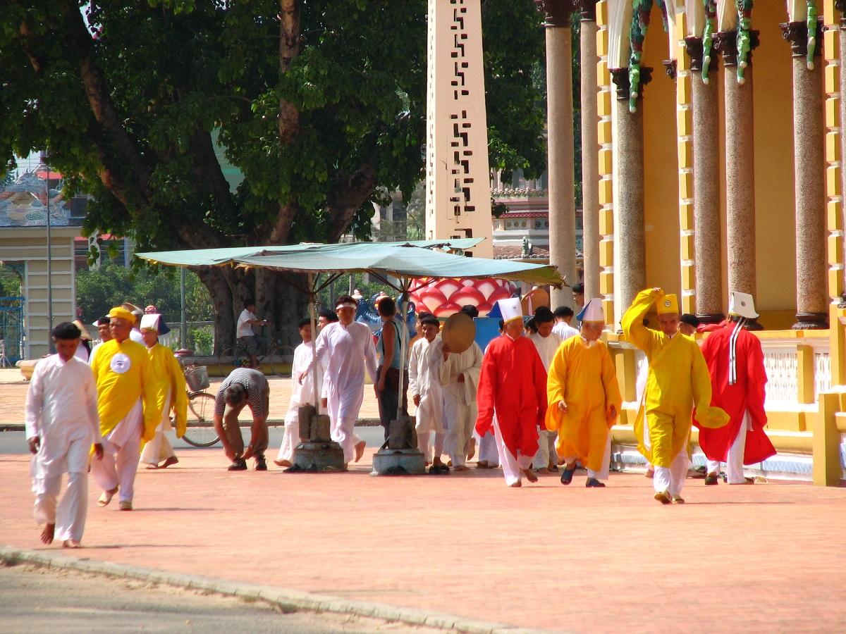 Kněží a stoupenci náboženství před chrámem Cao Dai