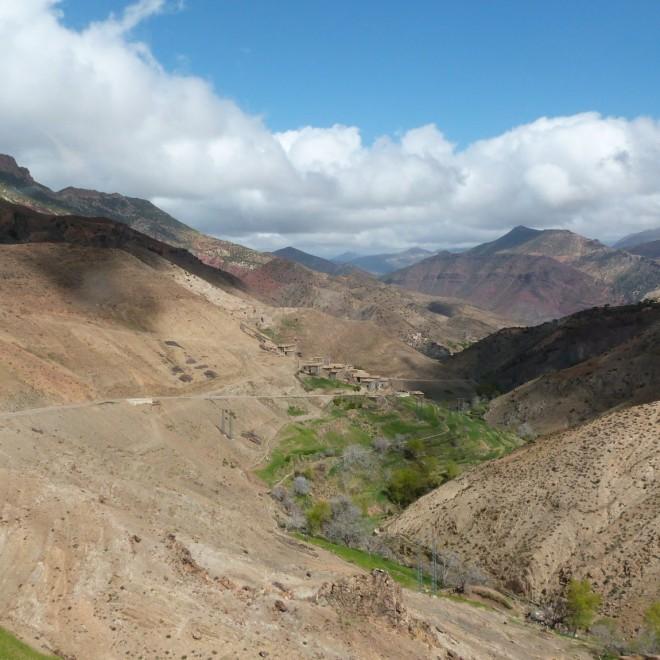 Výhled z vrcholků hor na malou vesnici.