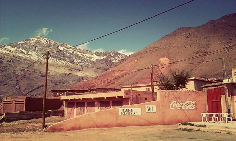 Reklama Coca Cola na zídce před domem, v pozadí kopec a zasněžená hora.