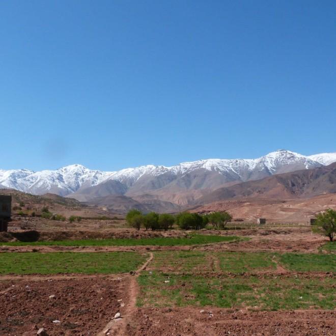 Vesnice se zasněženými horami v pozadí.