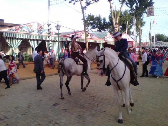 Koně s profesionálními jezdkyněmi tančící Sevillanu během Feria de Abril