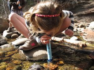LifeStraw Personal - holčička pije z potoka