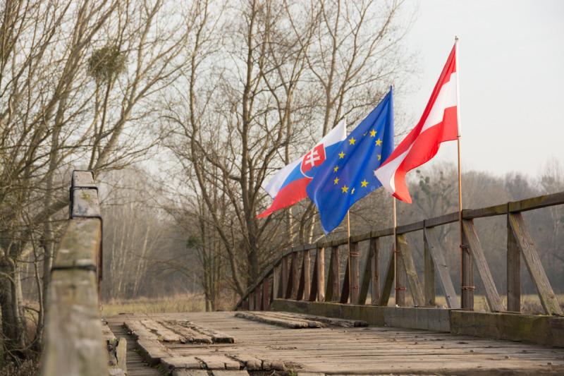 Detailní pohled na vlajky Slovenska, Evropské unie a Rakouska na dřevěném mostě k Pohansku.
