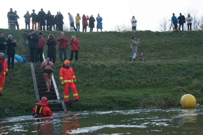 Záchranáři čekají jak ve vodě, tak u břehu na pomoc plavcům, aby jim v silném proudu pomohli ven z vody.