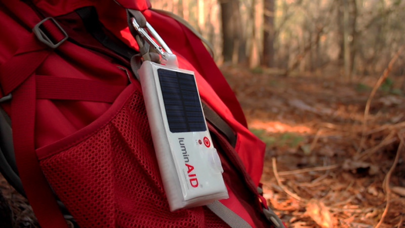 LuminAID - solární vodotěsná LED baterka v sáčku ve sbaleném stavu, zavešená na batohu.