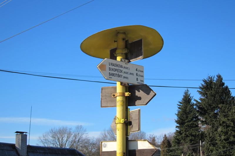 Směrovka z Pohořan na Svatý Kopeček. Zřejmě tu došlo k přeznačení, kousek za rozcestníkem už jsou červené značky.