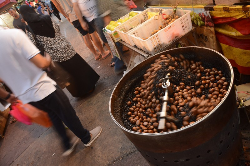 Kuala Lumpur, Malajsie - Pečení kaštanů na čínské tržnici.