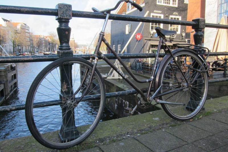 Postarší, jednoduše vybavené a tedy ideální kolo do amsterdamských ulic (v pozadí dům z roku 1695, křivý jako jeden z mnoha dalších)