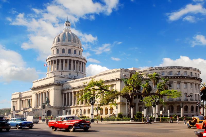 Historické americké auto před budovou Capitolio v Havaně na Kubě na náměstě Plaza de la Catedral.