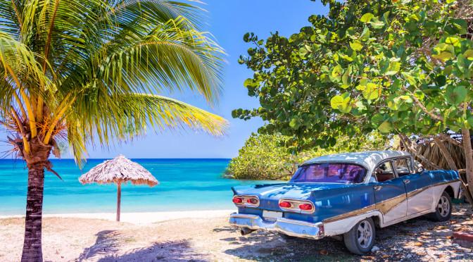 Historické americké auto zaparkované na pláži na Kubě.