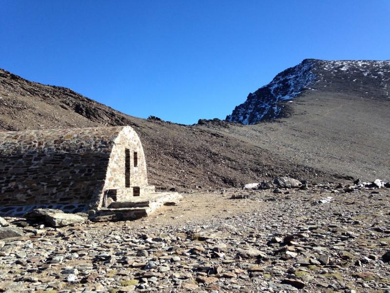 Chatka Refugio Vivac de la Caldera, kde jsme před výstupem nechali bagáž. V dáli je vidět Mulhacén.