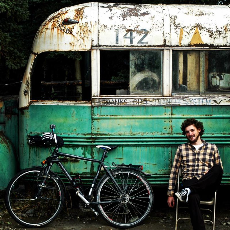 I, Cycleast –Matěj Balga před proslulým autobusem z filmu Útěk do divočiny, ve kterém si v divoké krajině Aljašky žil Chris McCandless svůj vysněný život dobrodruha.