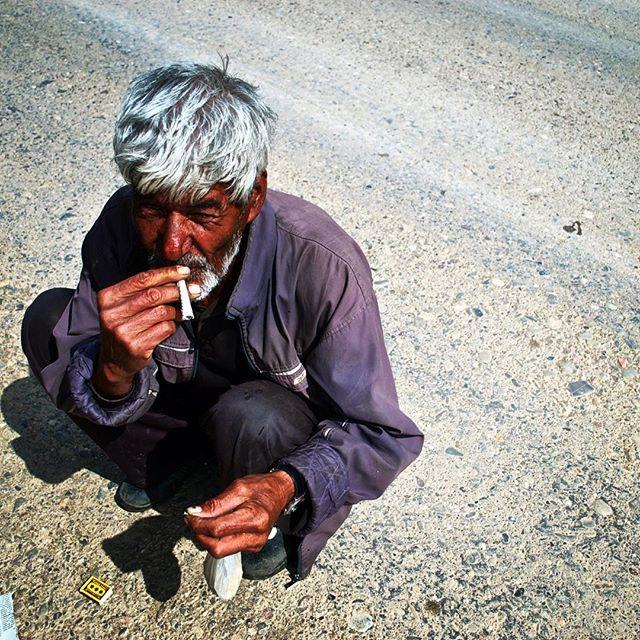 Místní rolník roluje mochorku do novin, aby si mohl zakouřit. Turkmenistán, březen 2014.