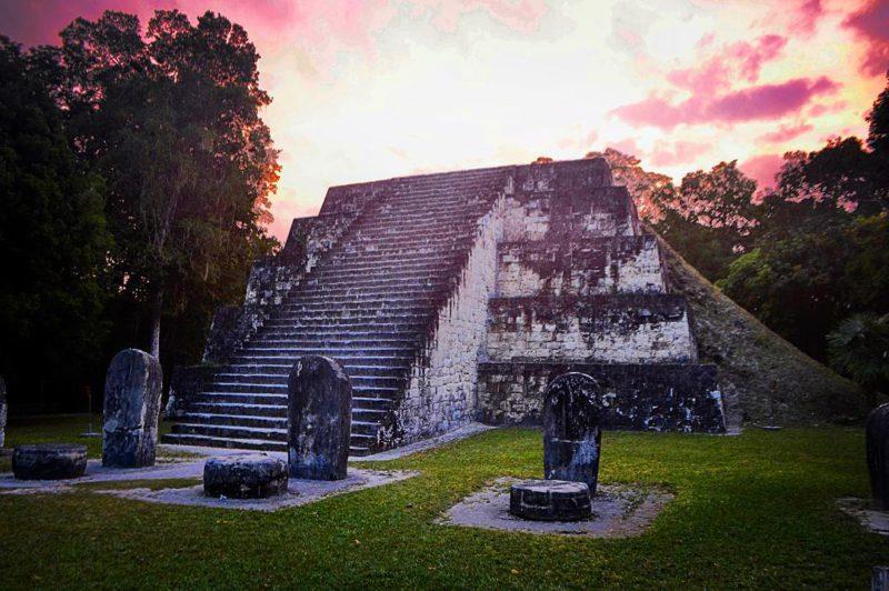 Západ slunce za pyramidou v dávném městě Mayů Tikal, Guatemala.