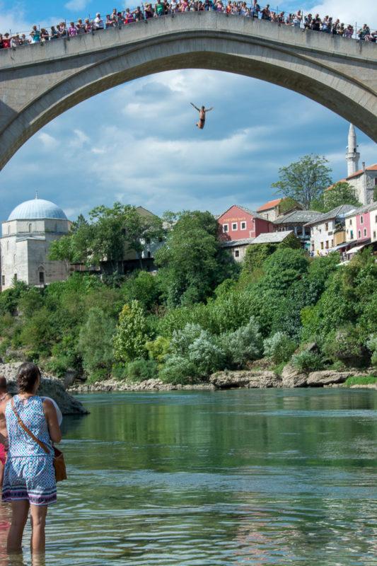 Mostar. Davy lidí na mostě i pod ním sledují odvážného skokana.